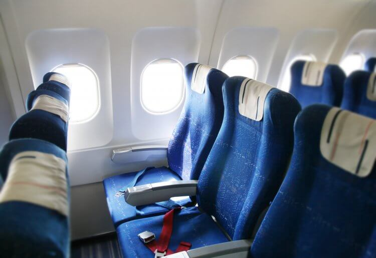 Interior of an airplane with three blue seats in each row with red seat belts and white windows open with light streaming inside.