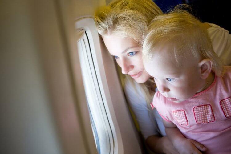 A blonde mother with a blonde baby sitting on an airplane looking out the airplane window.