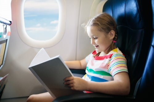 Girl sitting on a plane with braids in her hair. She is reading a book.