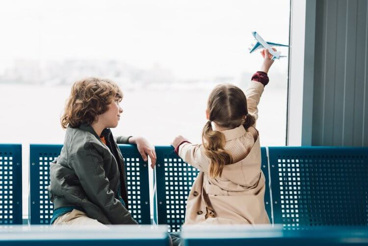 Two older children, a boy and a girl sitting inside an airport looking out the windows. The girl has a toy airplane in her hand flying it in the air.