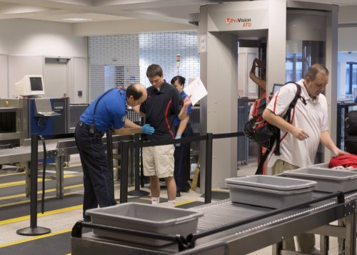 Travelers pass through the ProVision ATD Image-Free Scanner, a new technology used at security checkpoints which can automatically detect concealed objects made of any type of material.