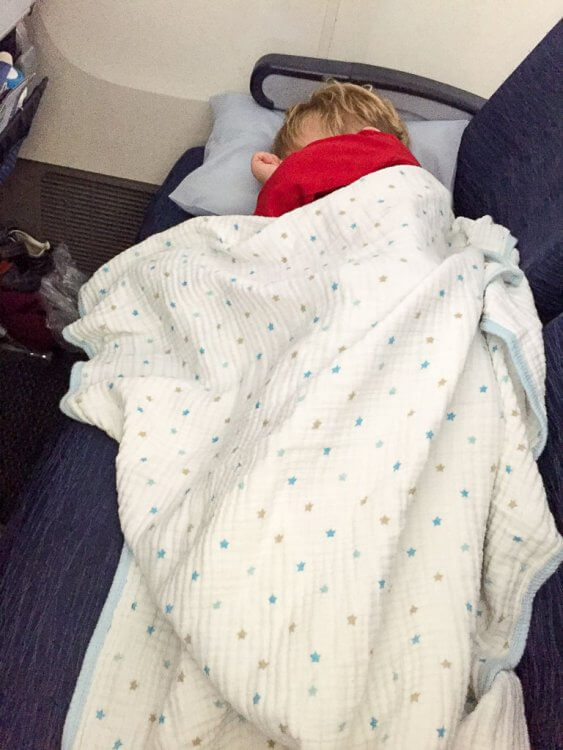 Little boy sleeping on an airplane with a pillow and a blanket.