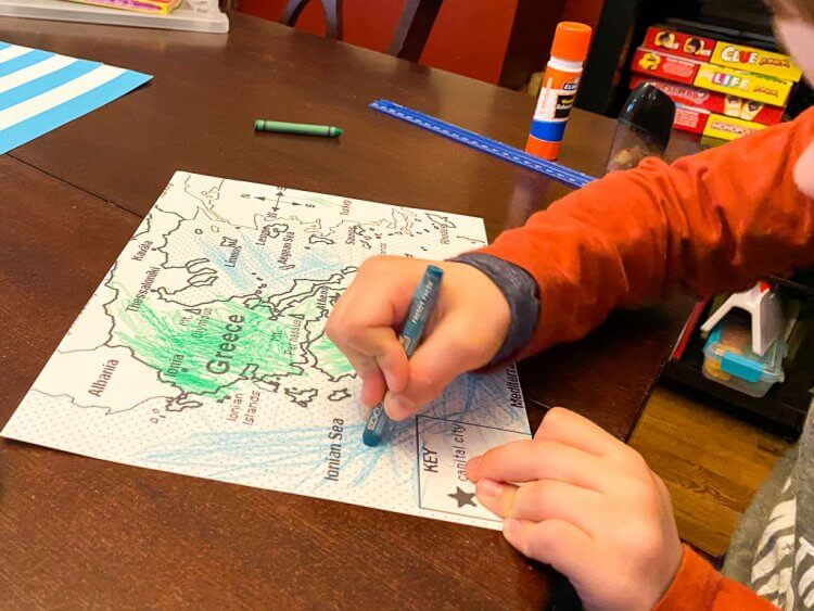 Boy with orange shirt coloring a map of Greece.