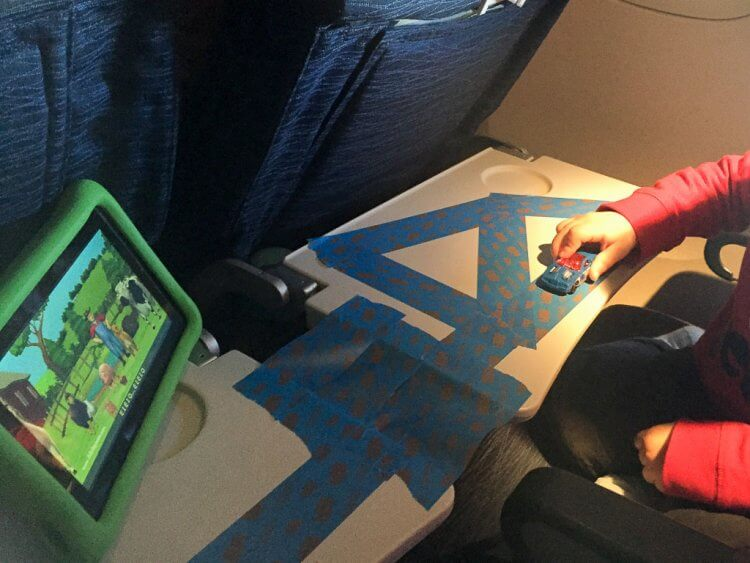 Little boy listening to songs playing on his tablet while playing with his cars on blue tape on a tray table on an airplane.