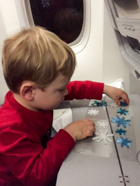Little boy playing with window clings on the tray table of the airplane.