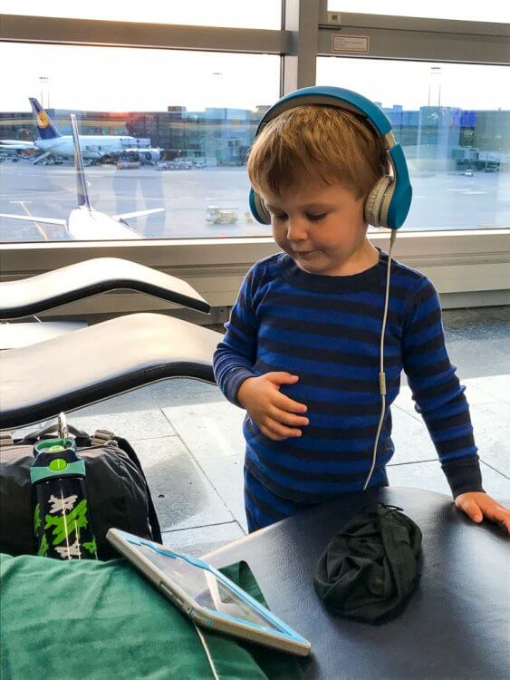 Little boy in the airport with headphones watching a show on his tablet.