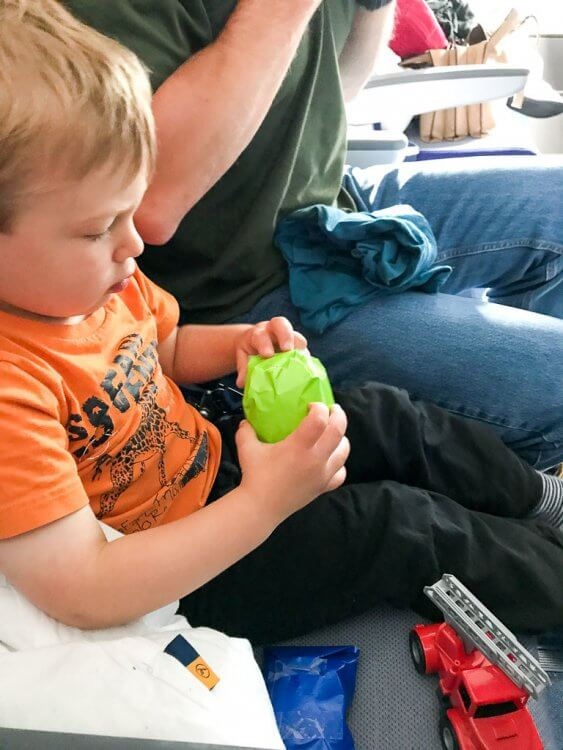Little boy opening a toy that is wrapped in green wrapping paper in his airplane seat.