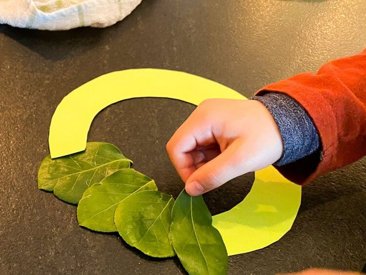 Gluing the leaves to a ring made out of paper to form a wreath.