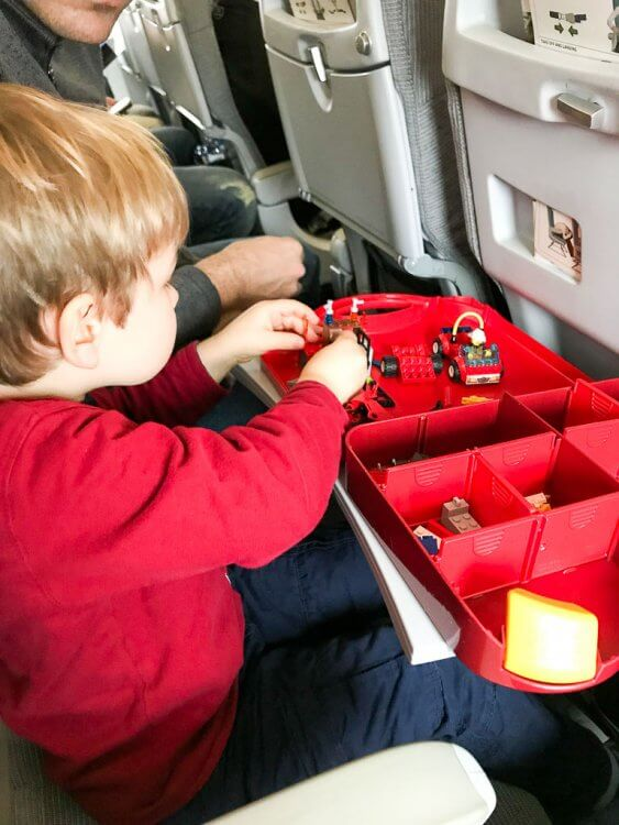 Little boy in a red shirt playing with a container of legos inside a plane. Toddler Airplane Toys.