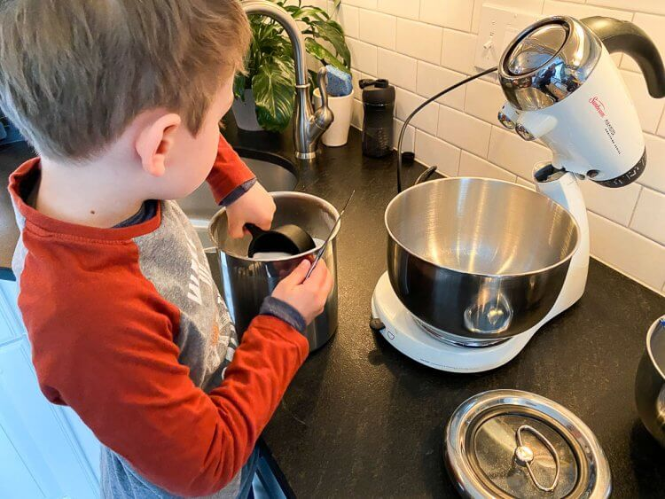 Making Greek cookies using a mixer in the kitchen with a little boy.
