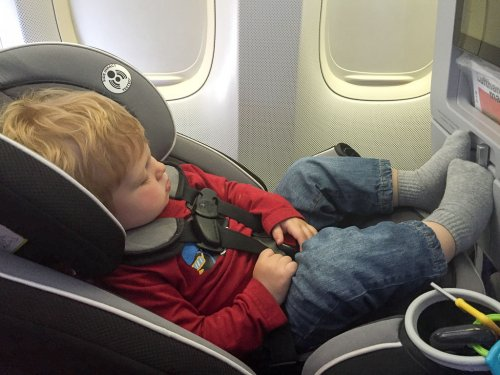 Toddler sleeping on a car seat that has been installed on an airplane.