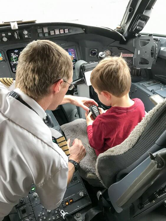 Little boy sitting in the cockpit with the pilot on a commercial jet.