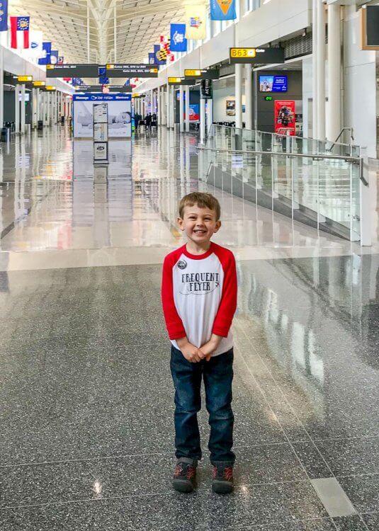 """Little boy wearing a """"frequent flier"""" shirt inside an airport."""