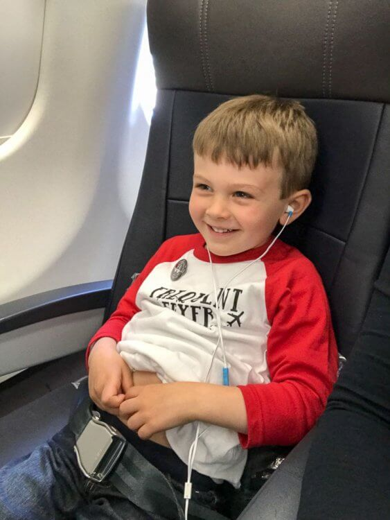 """Little boy sitting on the airplane with a """"frequent flier"""" shirt and earbuds in his ears."""