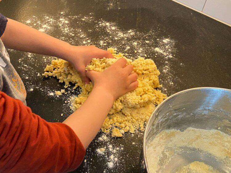 Little boy kneading the dough.