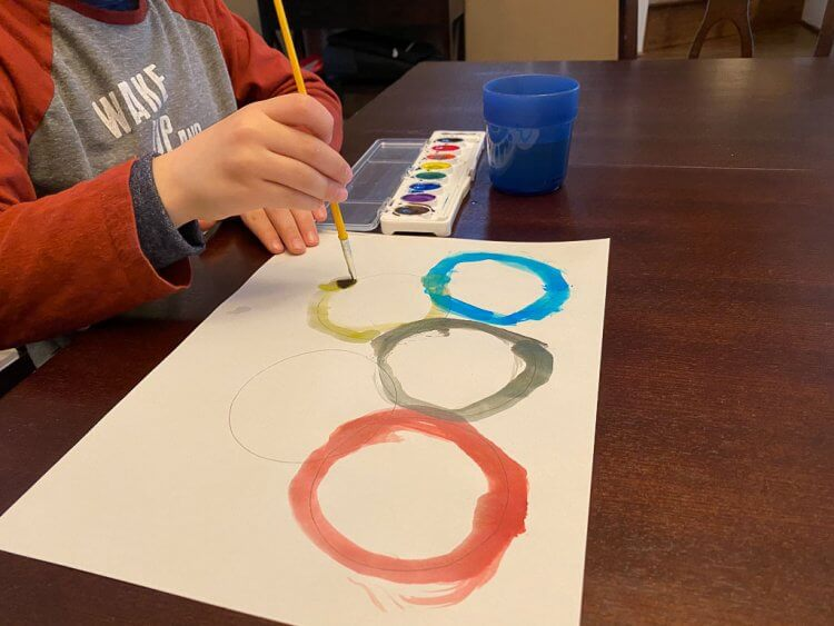 Boy drawing the olympic rings with water colors