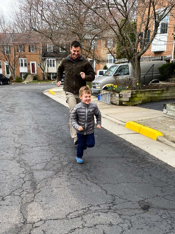 Father and Son having a race down the road near the house.