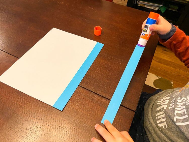 Child gluing blue strips of paper onto a white sheet of paper to make a Greek Flag.
