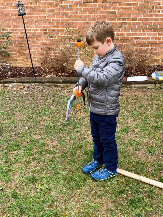 Little boy with a grey jacket getting ready to shoot an arrow.