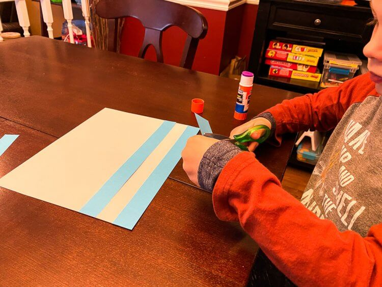 Child with orange sleeves gluing blue strips of paper to a white sheet of paper to make a Greek flag.