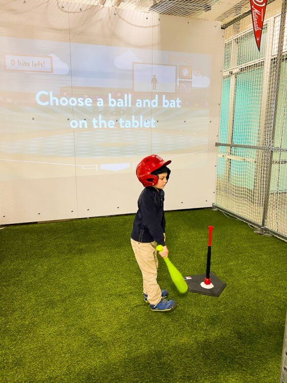 T-ball area with helmets, balls, bats and a virtual baseball screen.