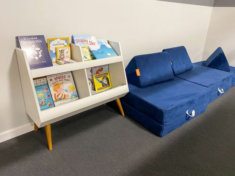 Reading zone in the toddler/baby area with a soft couch and books.