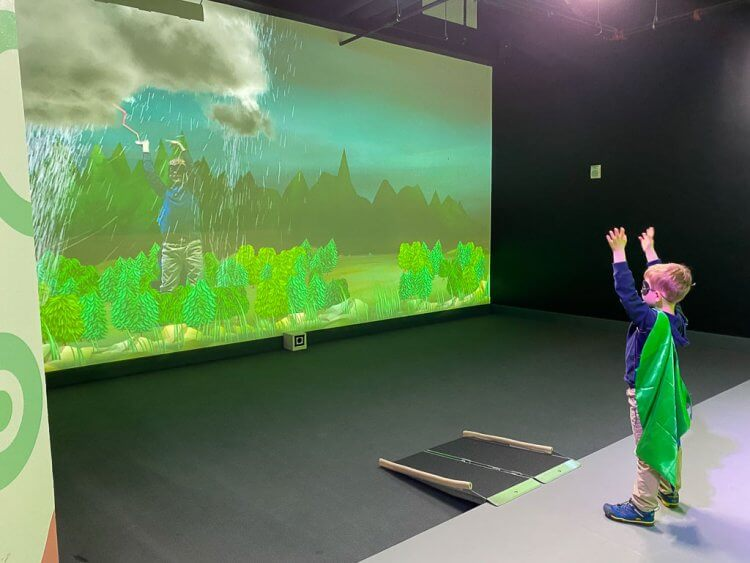 Interactive green screen where children can interact with the displays by moving their hands and body. The screen changes from spring/summer, winter and thunderstorms.