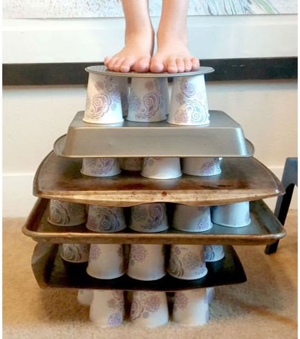 Boys feet standing on paper cups and cookie sheets stacked like the Ancient Greeks