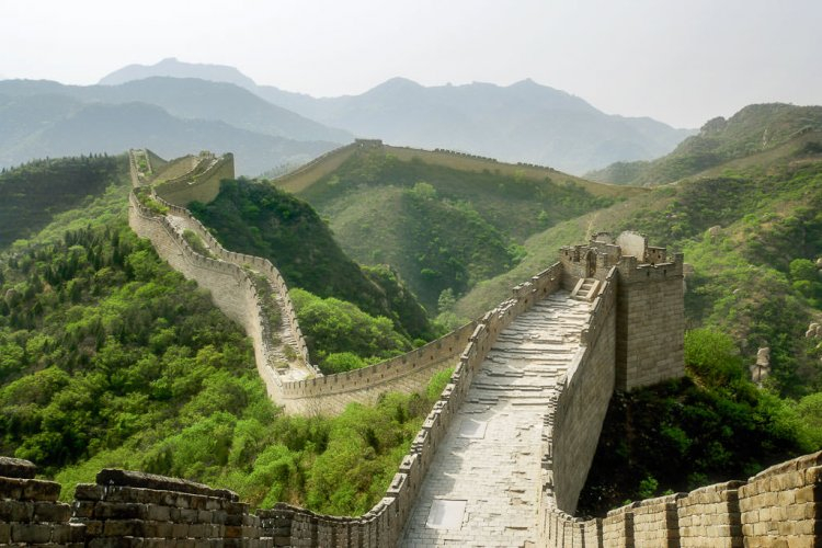 Great Wall of China standing in the center of the wall and looking towards the hills with the wall running in the front.