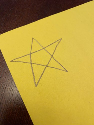 Hand drawn star on a piece of yellow construction paper.