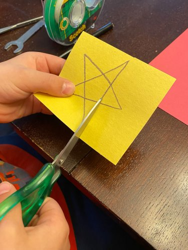 Little boy cutting out a yellow star on a piece of construction paper.