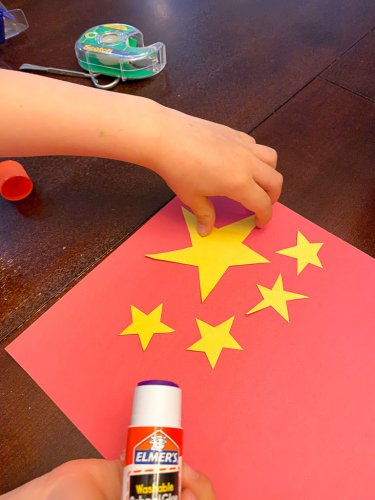 Little boy gluing down the yellow stars to the red background.