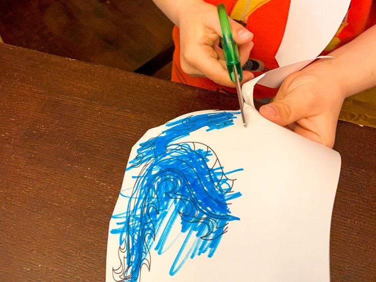Little boy cutting out his blue dragon.