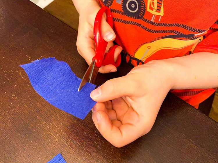 """Cutting a fray into a piece of 3"""" crepe paper."""