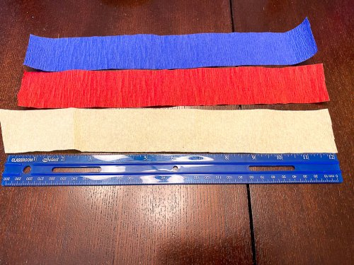 """Cutting three strips of crepe paper to 12"""" using a ruler."""