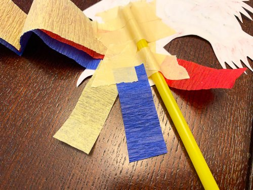 Taping little fringe pieces of party streamers to the dragon's tail.