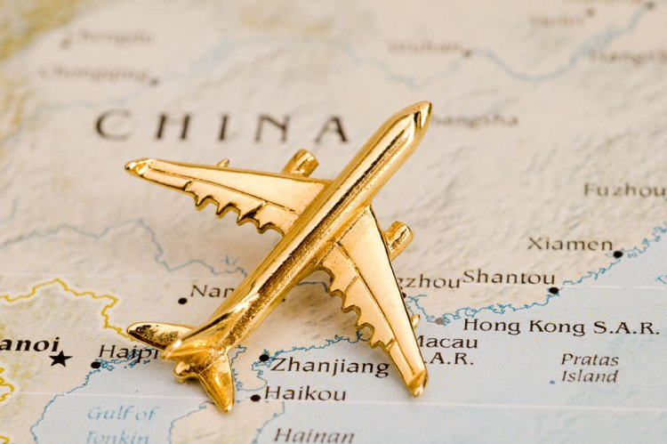 Gold airplane sitting on a map of China.