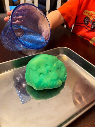 Ball of play-doh in the center of the tray with a little boy holding a cup of water over the top.