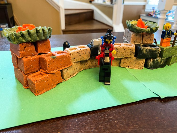 Bricks made out of play doh to make the great wall of china model. LEGO Minifigures sit in the front and on the walls to guard.