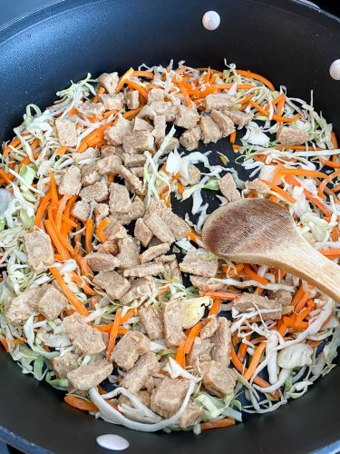 Sauteing the carrots, cabbage and plant based chicken in some vegetable oil.