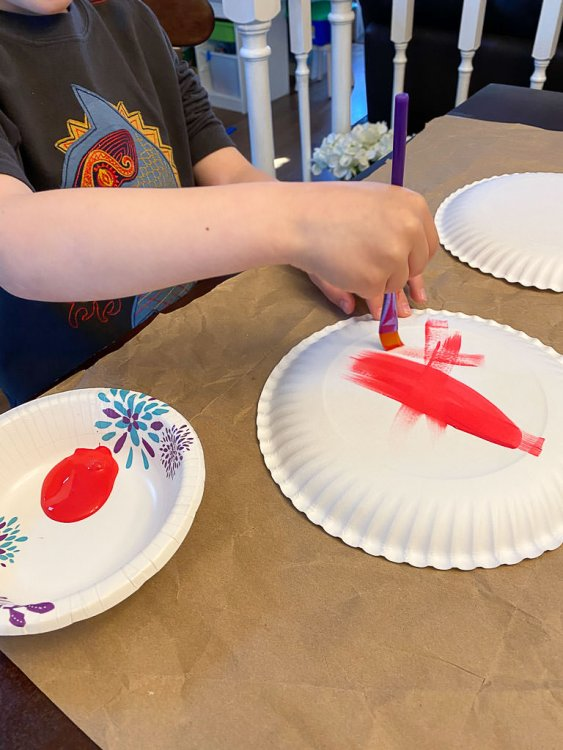 Boy painting the back of a paper plate with red paint.