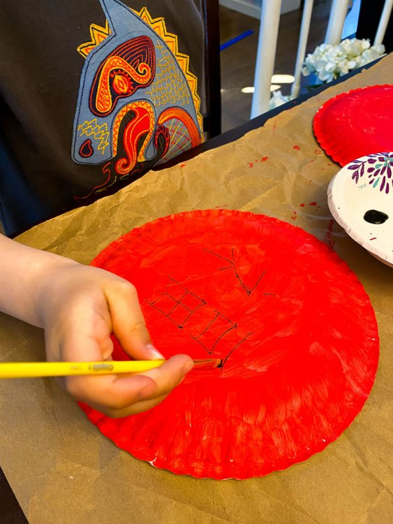 Little boy's hand painting a chinese character on the back of a paper plate.