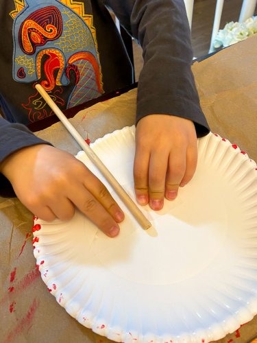 Little boy adding a wooden dowel to the front of the paper plate and taping it down.