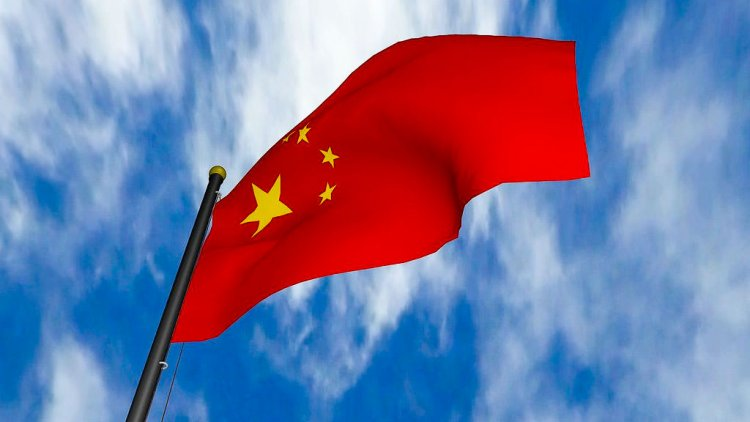 Chinese flag with a red background, a large star in the left hand corner and four smaller stars surrounding the larger star.
