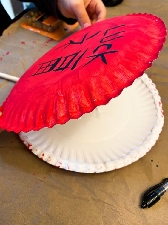 Gluing the two paper plates together (on top of each other).