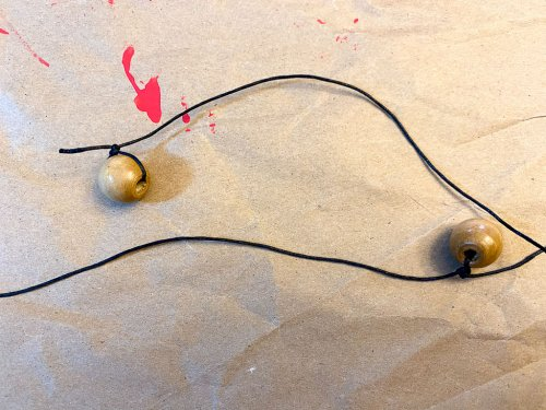 Tying the wooden bead to the string.