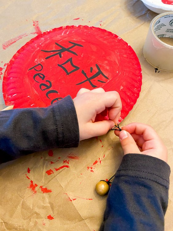 Tying the string to the paper plate on the side.