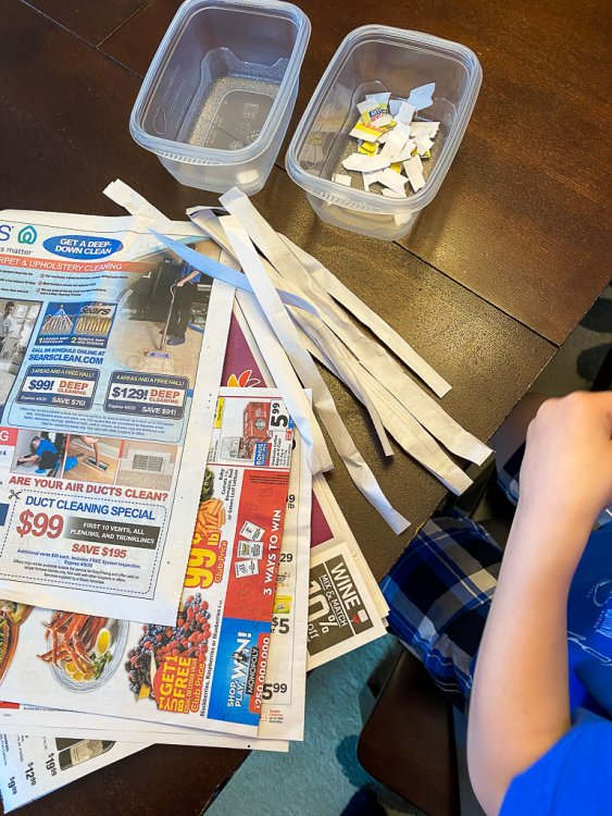 Cutting strips of newspaper and adding little pieces into the containers.