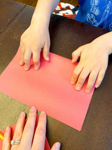 Folding a piece of red construction paper in half.