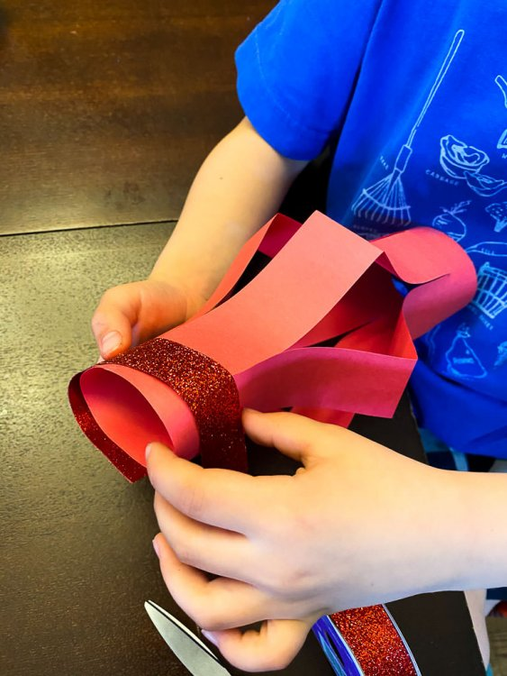 Little boy adding sparkly red ribbon to his Chinese Paper Lantern Craft.
